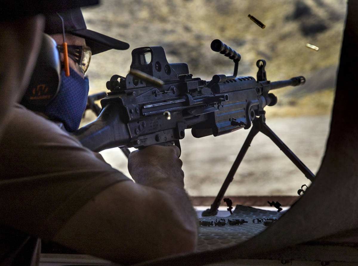 Christopher Lawrence fires an M249 Saw machine gun on the Adrenaline Mountain gun range, Thursd ...