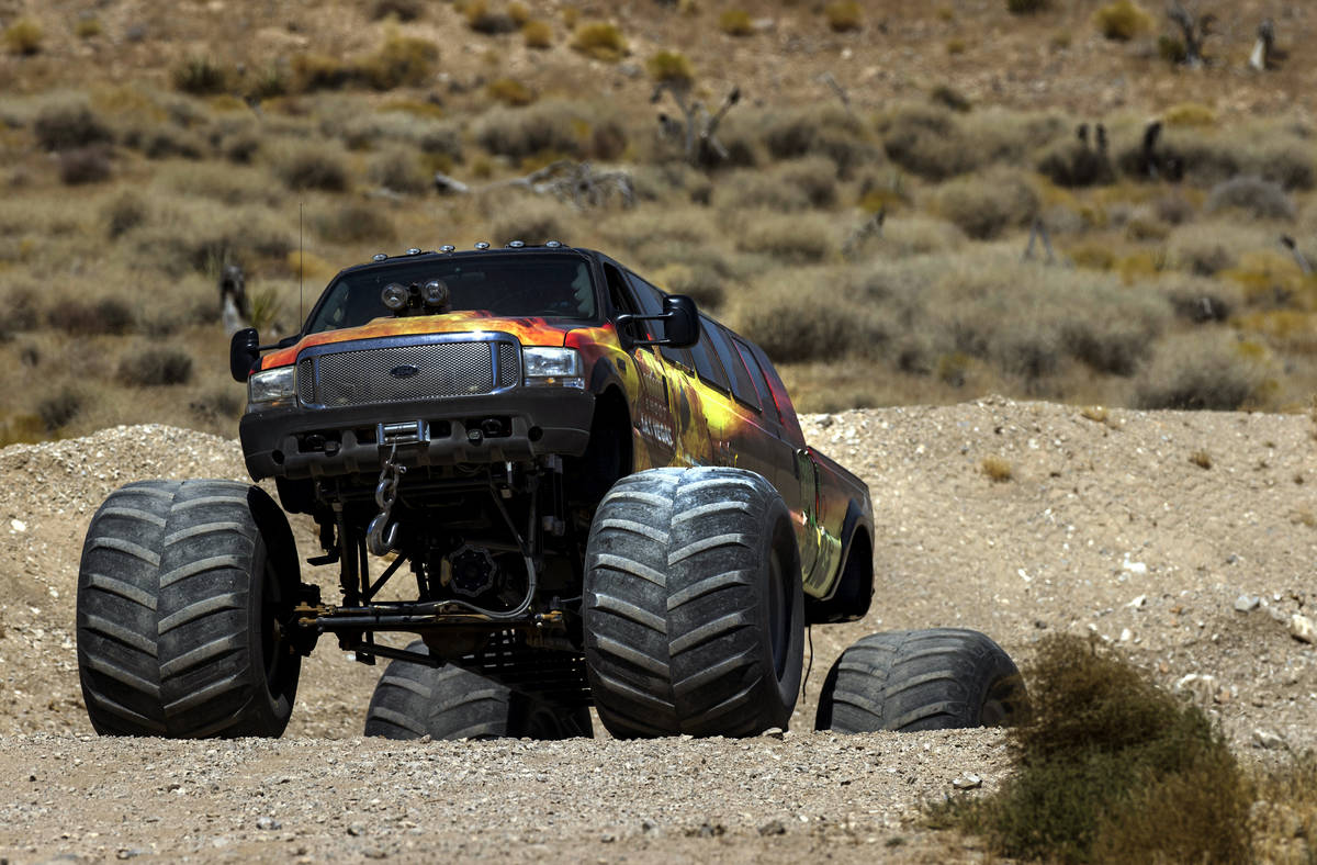BIG GUNS, the world's longest monster truck, digs in the dirt while navigating a hill at Adrena ...