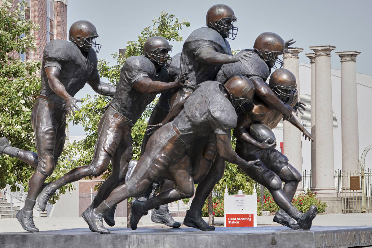 A hand sanitizing station is placed behind a statue of football players outside Memorial Stadiu ...
