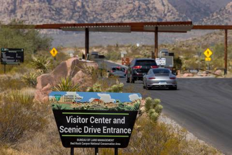 An entrance marker and vehicles for the Red Rock Canyon National Recreation Area near Las Vegas ...