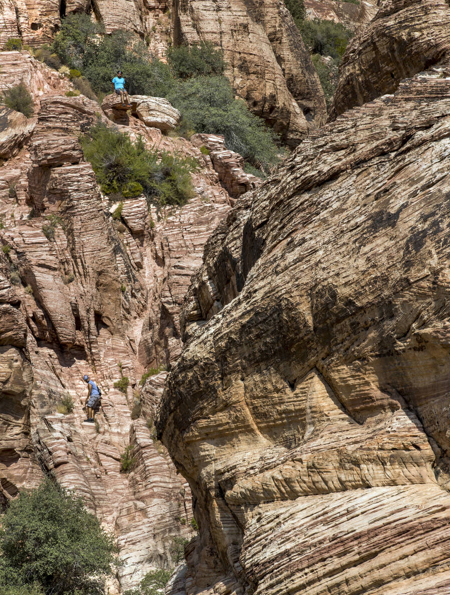 Fernando Espinosa, top, and Cesar Garcia of Chicago scale a ridge line about the Calico 1 trail ...