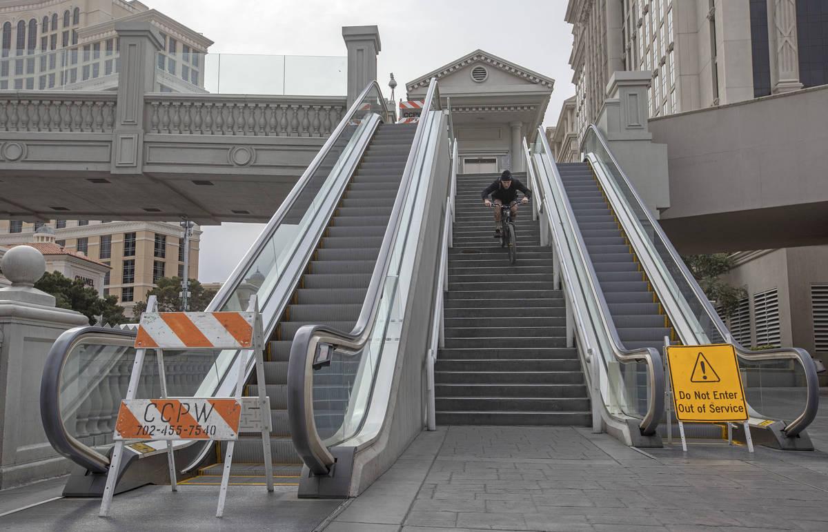 Las Vegan Matt Cremeans bikes down stairs of a pedestrian bridge on the Strip on Wednesday, Mar ...