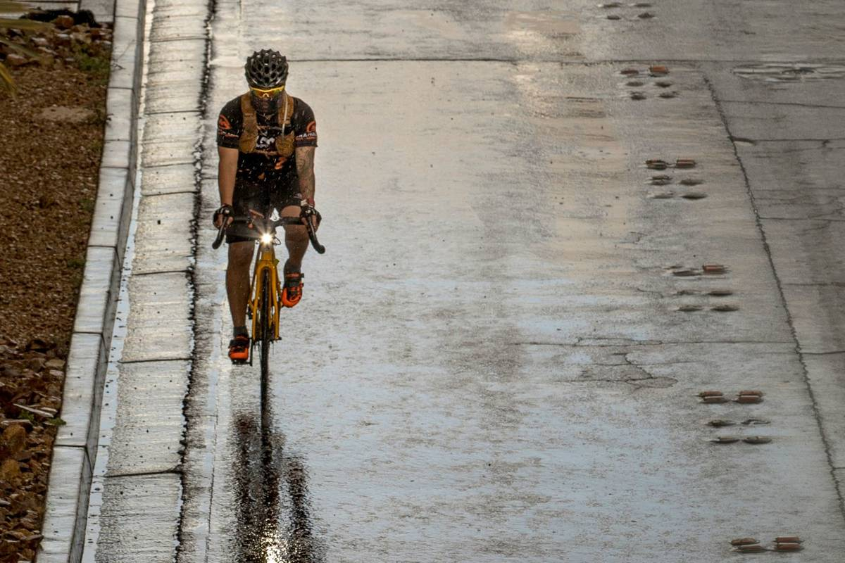 A cyclist wearing a face mask rides in the rain down the Las Vegas Strip past the Fashion Show ...
