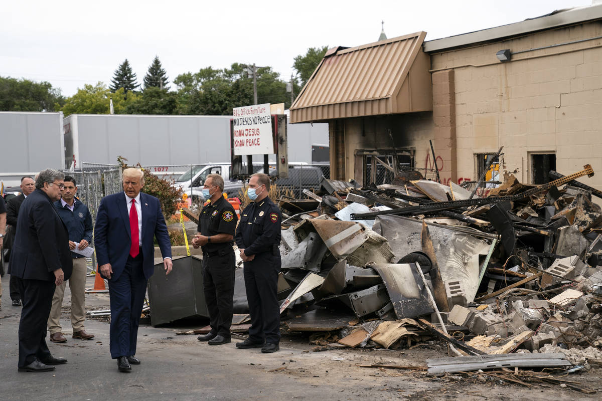 President Donald Trump walks Tuesday, Sept. 1, 2020, as he tours an area damaged during demonst ...