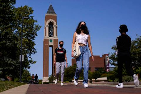 Masked students walk through the campus of Ball State University in Muncie, Ind., Thursday, Sep ...