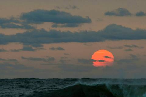 This photo taken at sunrise from Surf City on Long Beach Island in New Jersey shows the sun shr ...