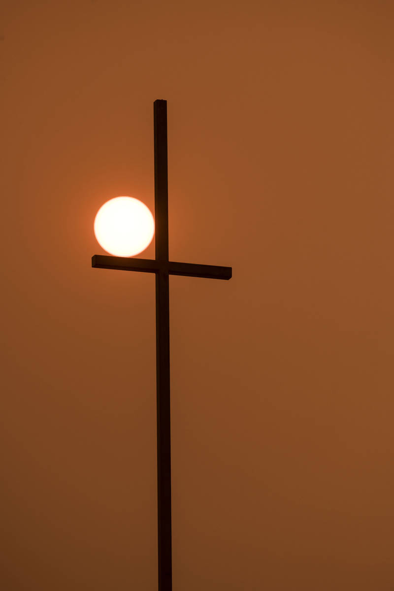 In a sky with wildfire smoke, the rising sun shines orange behind a church's cross in Walla Wal ...