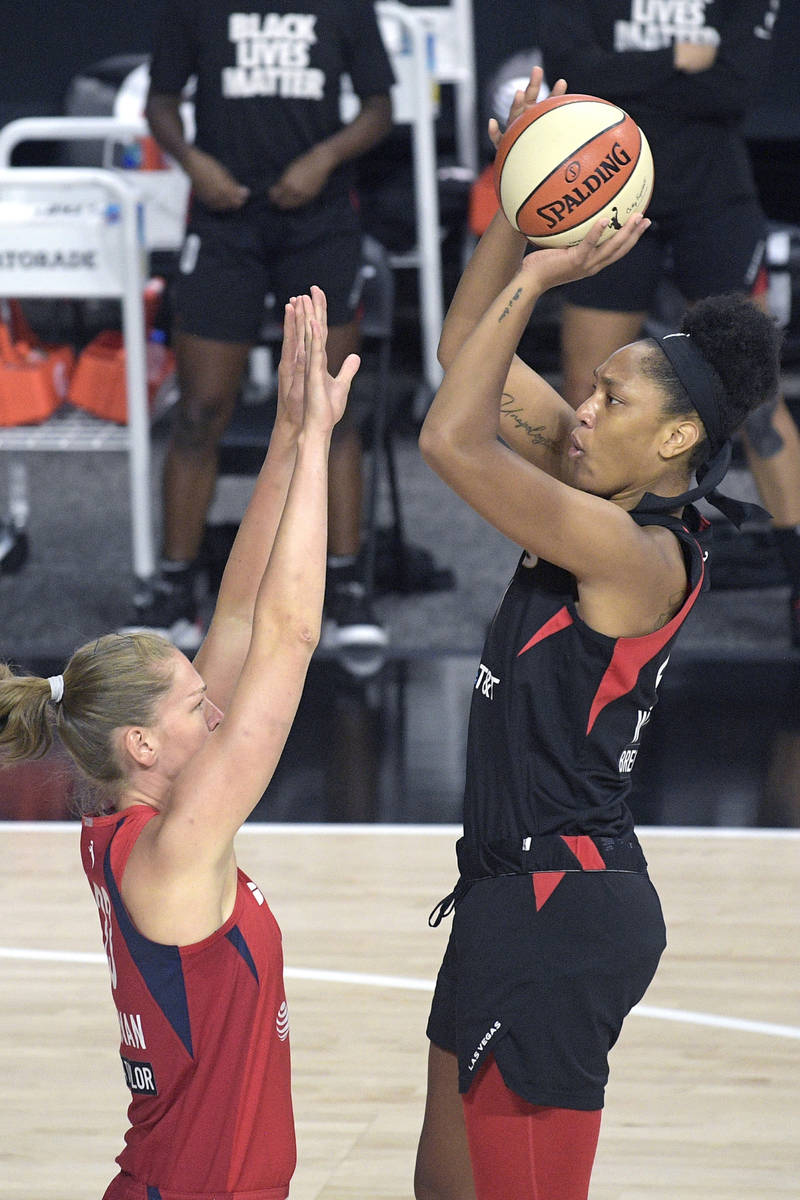 Las Vegas Aces center A'ja Wilson, right, goes up for a shot in front of Washington Mystics gua ...