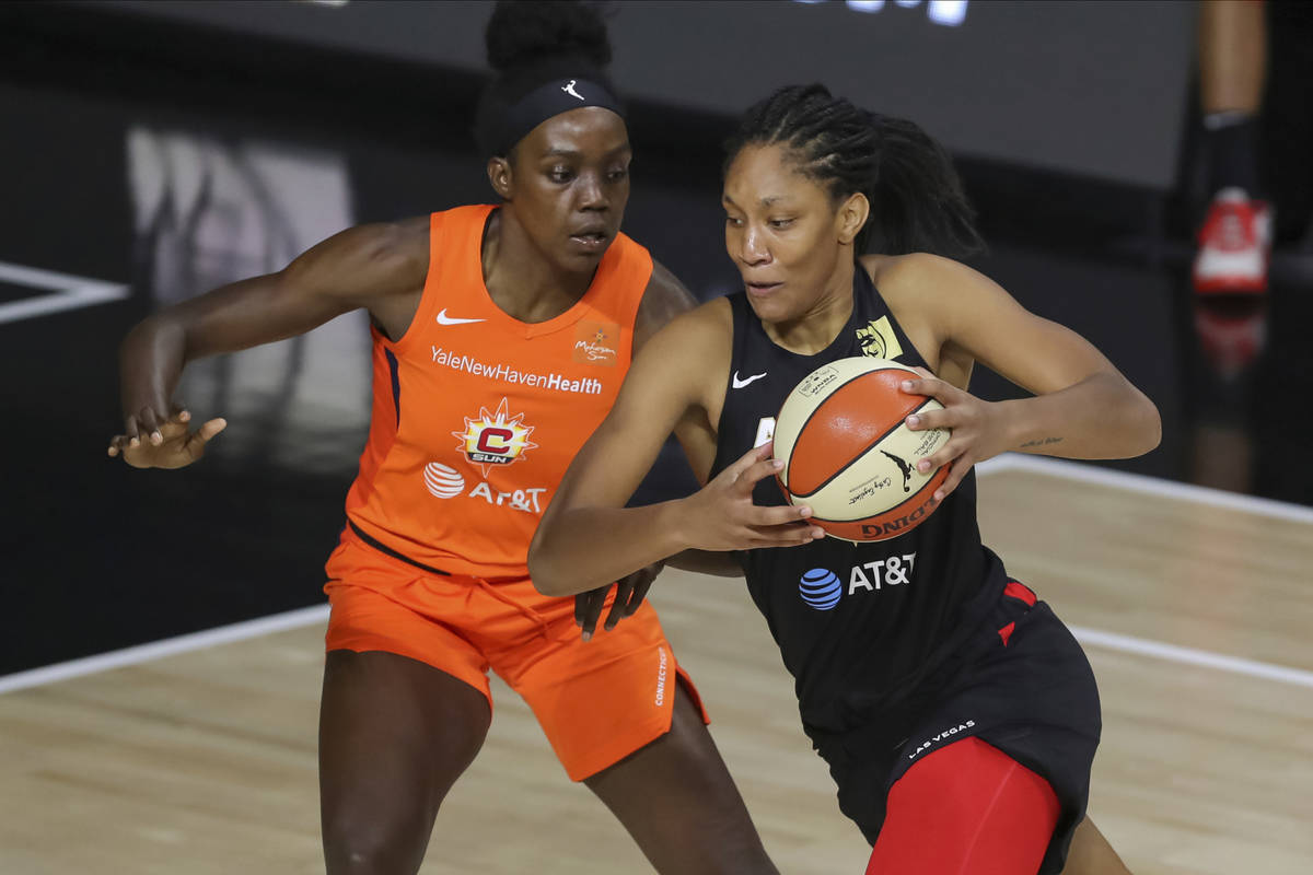 Las Vegas Aces' A'ja Wilson, right, drives against Connecticut Sun's Beatrice Mompremier during ...