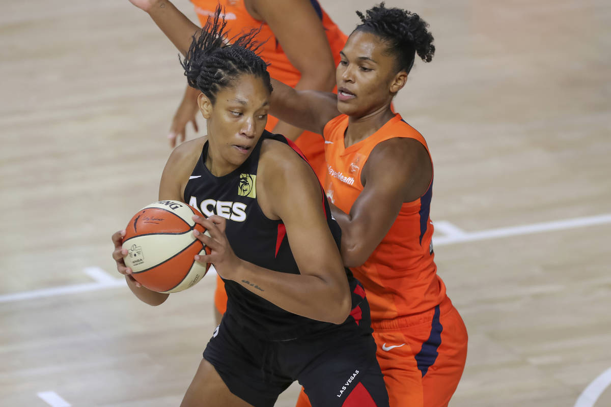 Las Vegas Aces' A'ja Wilson, left, drives against Connecticut Sun's Alyssa Thomas during the fi ...