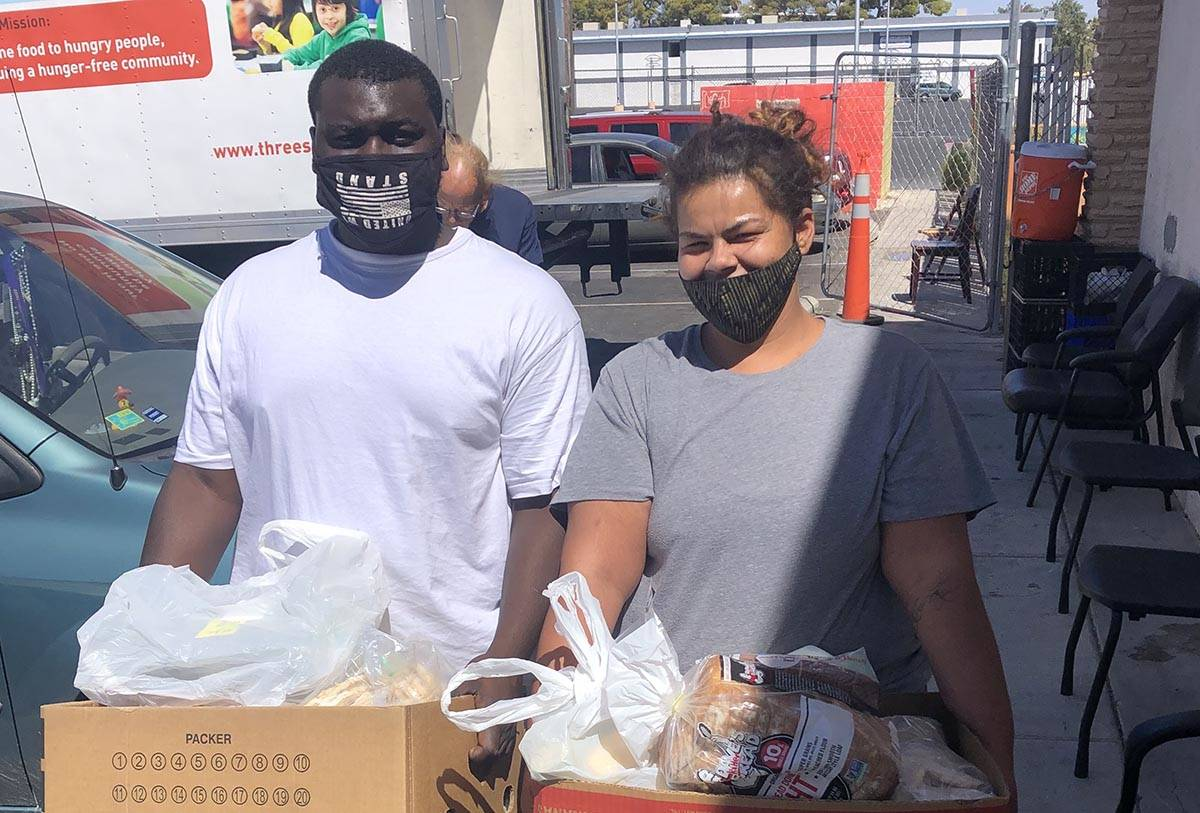 Lekarrie Evans and Lache Campbell pose with the food they received from City Impact's food bank ...