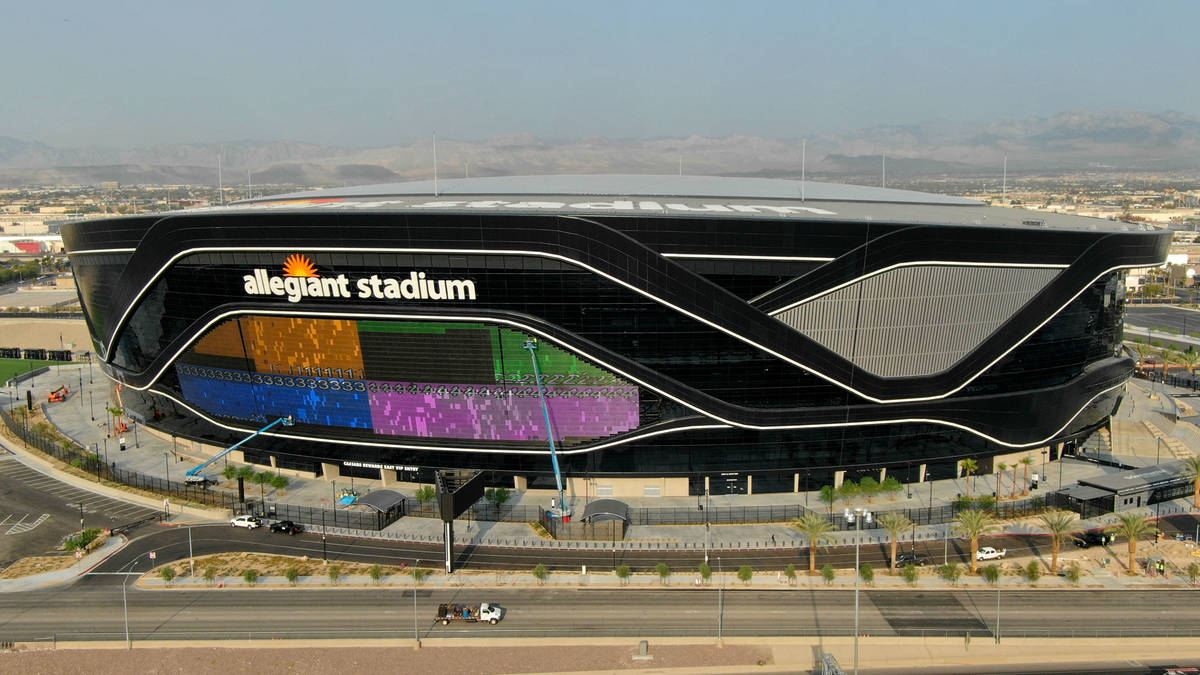 The massive 27,600-square-foot video board lights up with color on side of Allegiant Stadium th ...