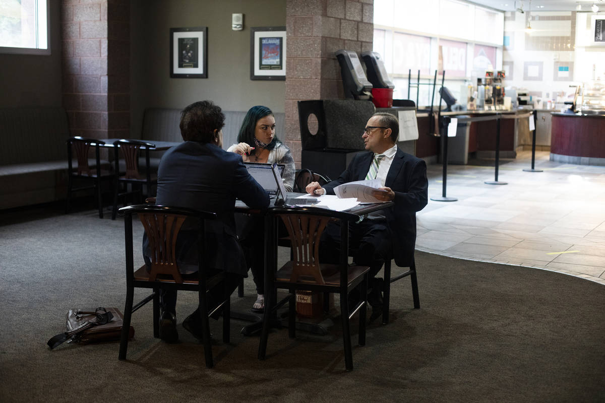 Alisha Burns speaks with her lawyer Tony Abbatangelo, right, and law clerk Robert Rose, left, b ...
