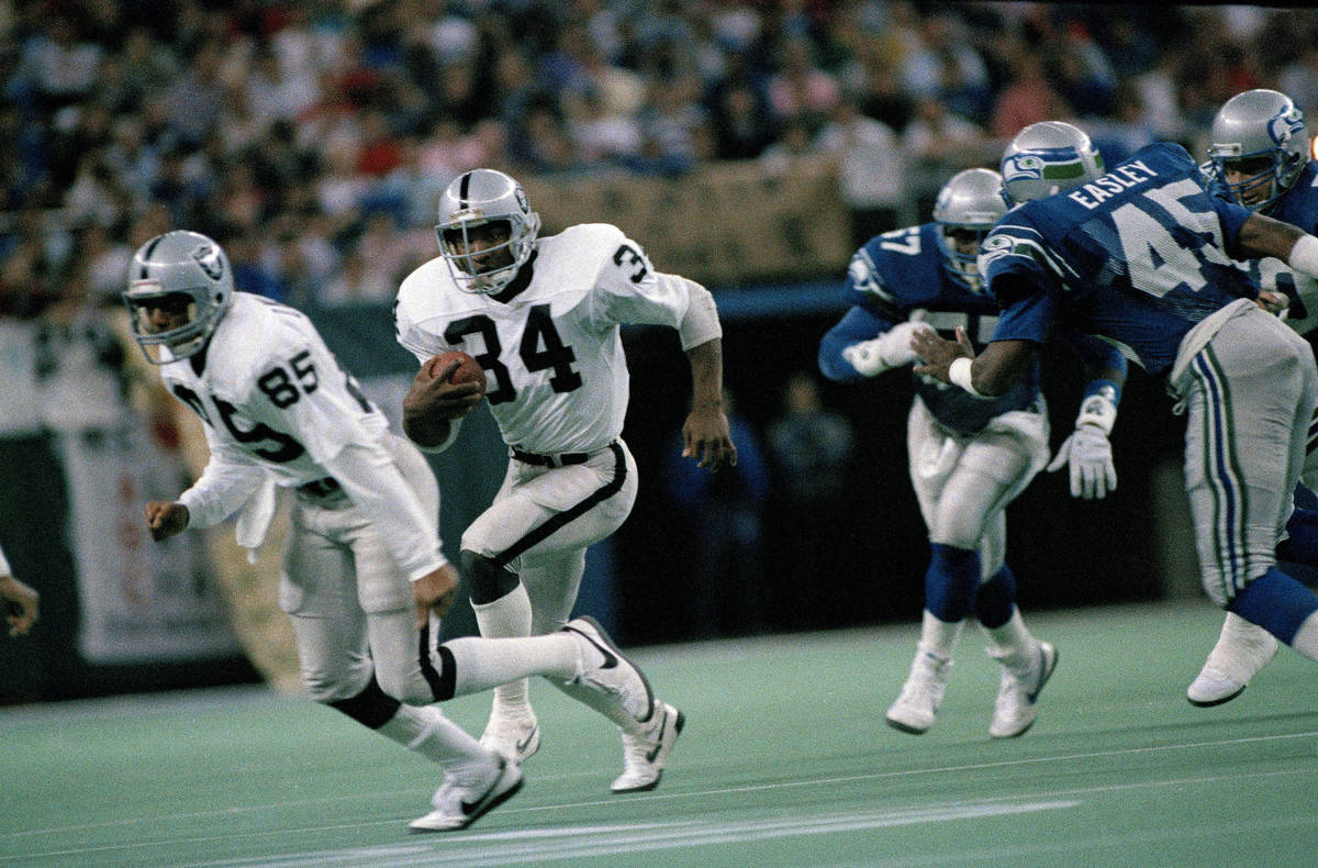 Running back Bo Jackson (34) of the Los Angeles Raiders follows Dokie Williams (85) for a four ...