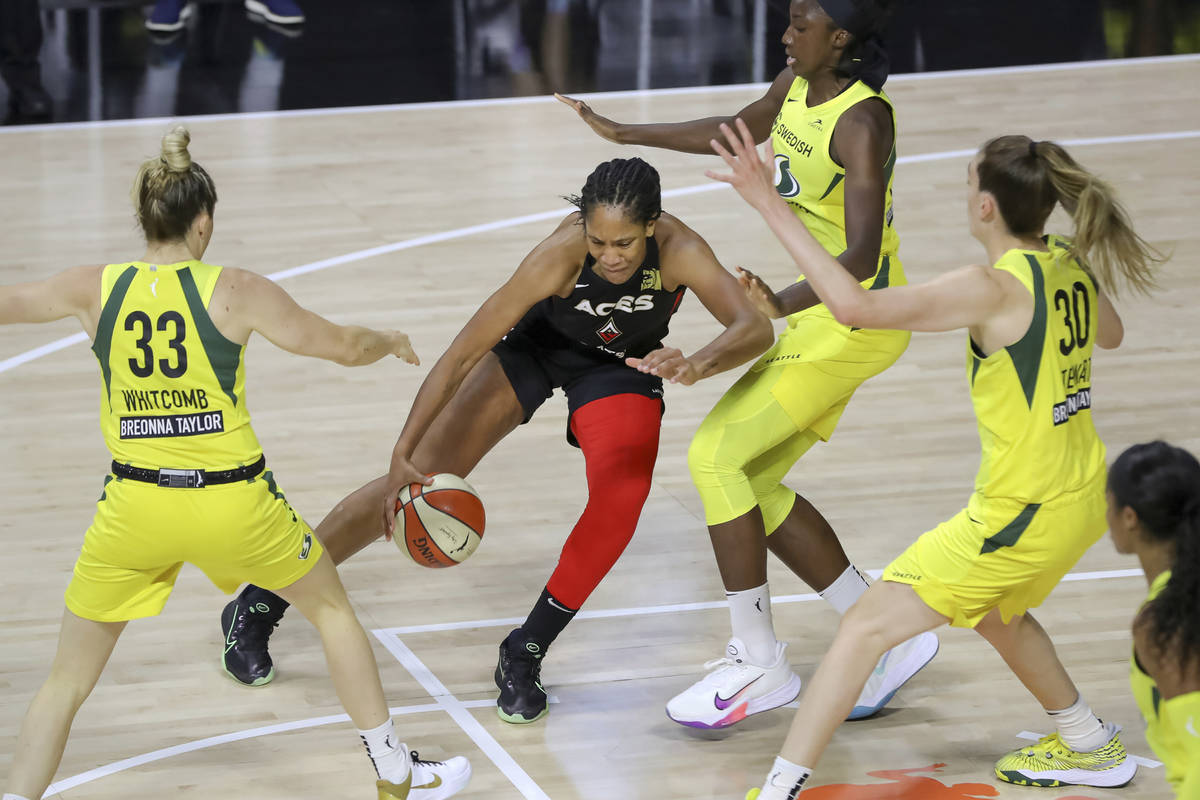 Las Vegas Aces' A'ja Wilson, center, drives against the Seattle Storm of, from left, Sami Whitc ...