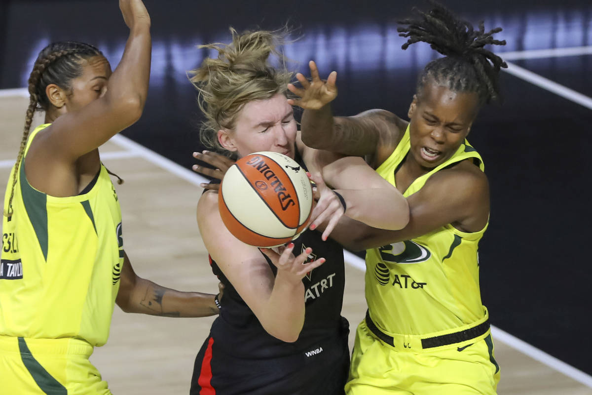 Las Vegas Aces' Carolyn Swords, center, collides with Seattle Storm's Epiphanny Prince, right, ...