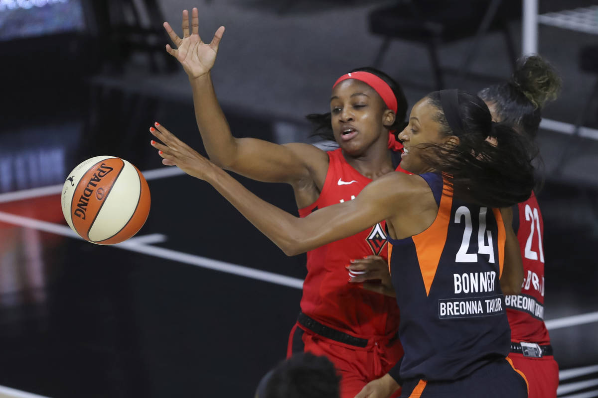 Connecticut Sun's DeWanna Bonner (24) and Las Vegas Aces' Jackie Young reach for the ball durin ...