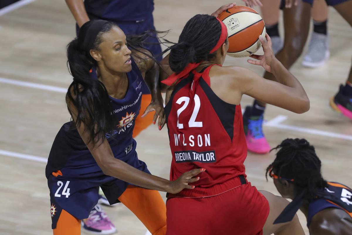 Las Vegas Aces' A'ja Wilson (22) drives against Connecticut Sun's DeWanna Bonner (24) during th ...