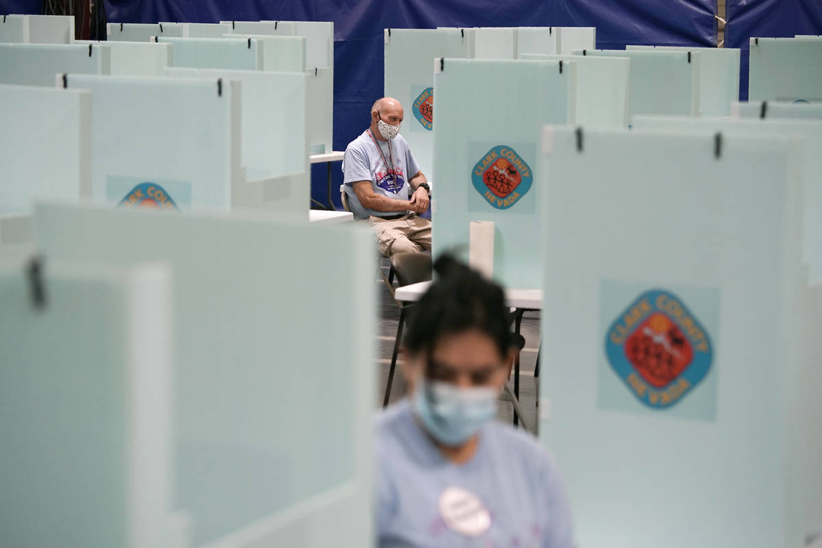 In this June 9, 2020, file photo, election workers staff one of a few in-person voting places i ...