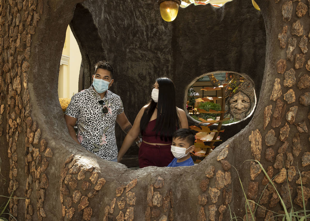 Chris Garcia, left, his wife Rae and his son Dex, 6, visiting from Texas, visit the new fall di ...