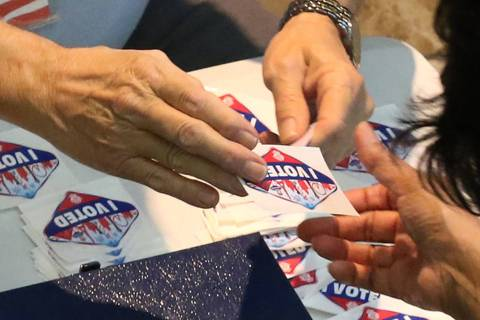 "A worker hands out ""I Voted "" sticker to a voter at a polling station at Galleria Mall on Tuesd ..."