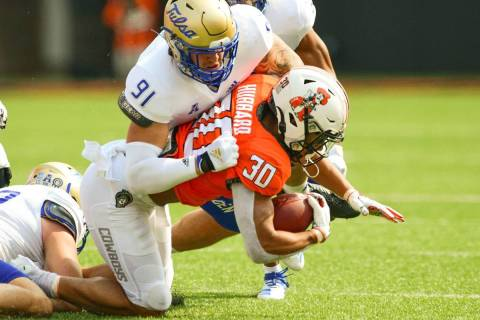 Tulsa defensive end Bryce Alonso (91) tackles Oklahoma State running back Chuba Hubbard (30) du ...