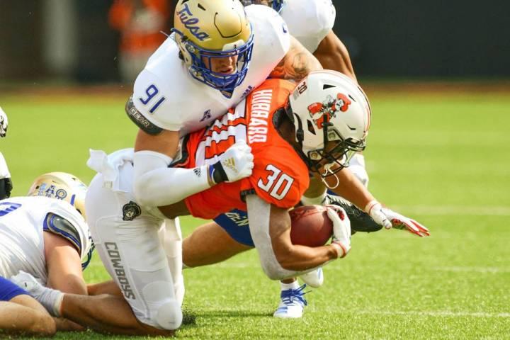 Tulsa defensive end Bryce Alonso (91) tackles Oklahoma State running back Chuba Hubbard (30) du ...