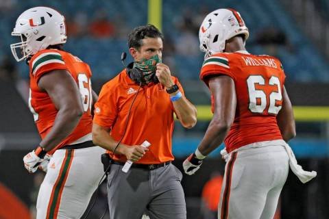 Miami coach Manny Diaz, center, walks on the field during an NCAA college football game against ...