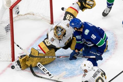 Vegas Golden Knights goalie Marc-Andre Fleury (29) makes a save on Vancouver Canucks' Jake Virt ...