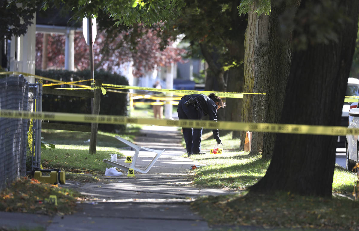 A Rochester police technician picks up some items as evidence near the home where a fatal house ...