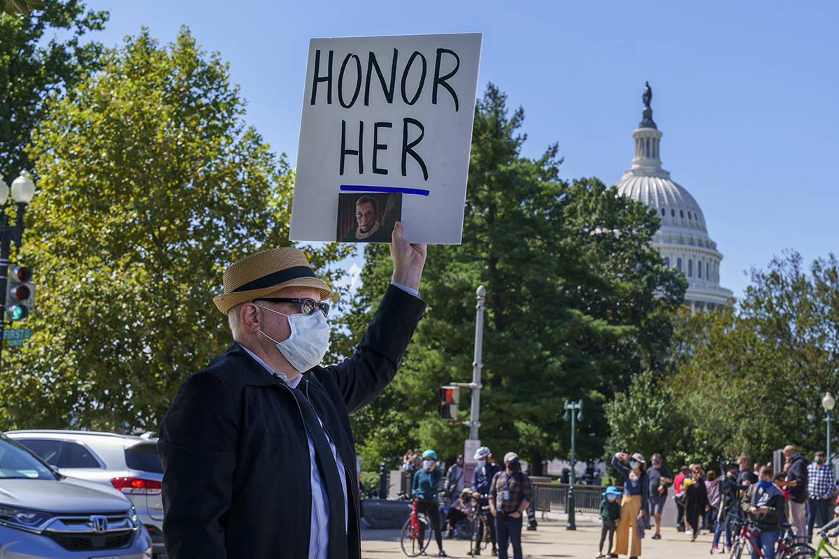 A man holds up a sign in honor of the late Justice Ruth Bader Ginsburg, as people gather at the ...