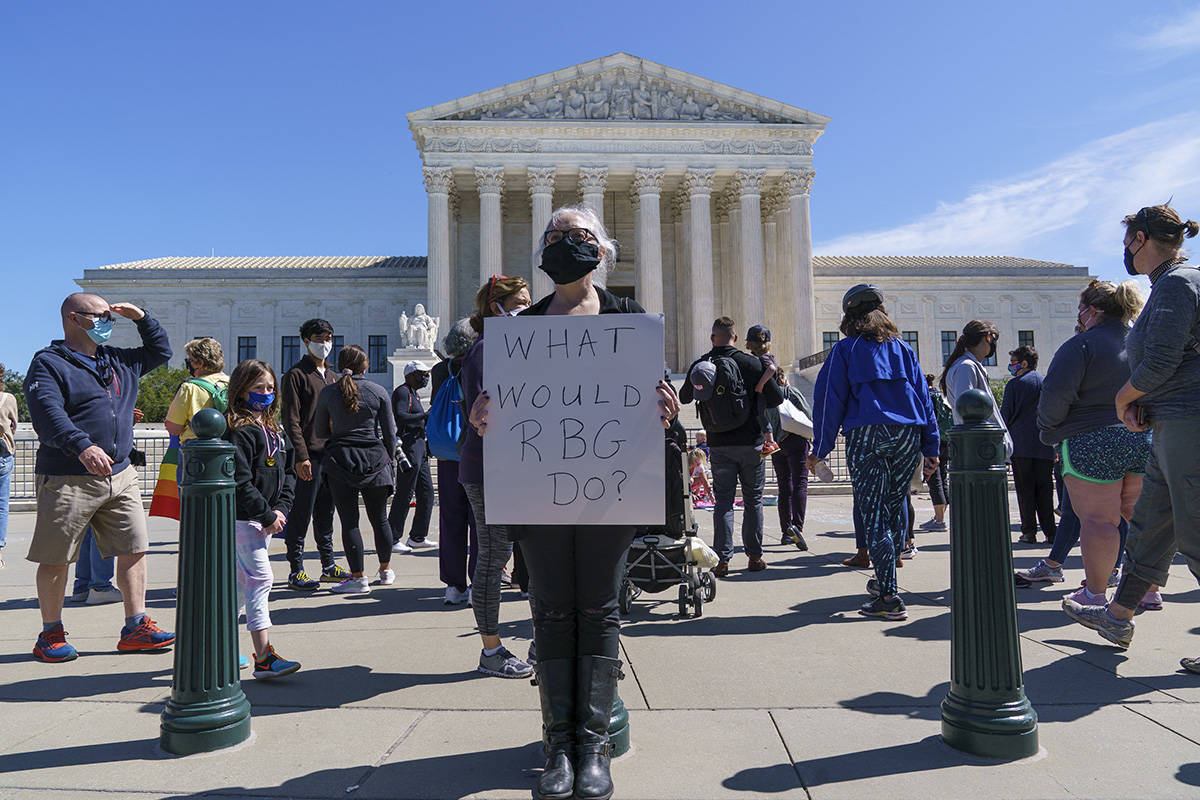 Kelli Midgley, center, an English teacher from Baltimore, joins people gathered at the Supreme ...