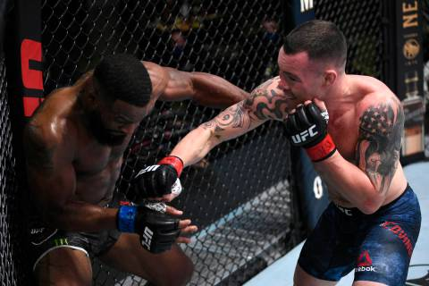 Colby Covington, right, punches Tyron Woodley in their welterweight bout during the UFC Fight N ...