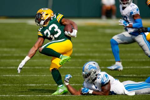 Green Bay Packers' Aaron Jones runs past Detroit Lions' Amani Oruwariye during the first half o ...