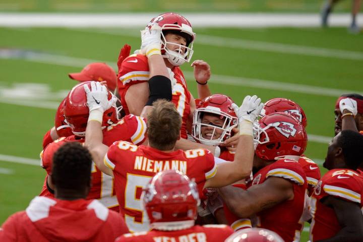Kansas City Chiefs kicker Harrison Butker, top, is lifted by teammates after making the game-wi ...
