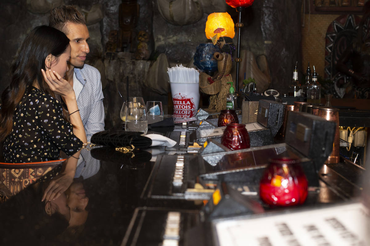 A couple enjoys tiki drinks at The Golden Tiki as bars reopened for the first time in months on ...