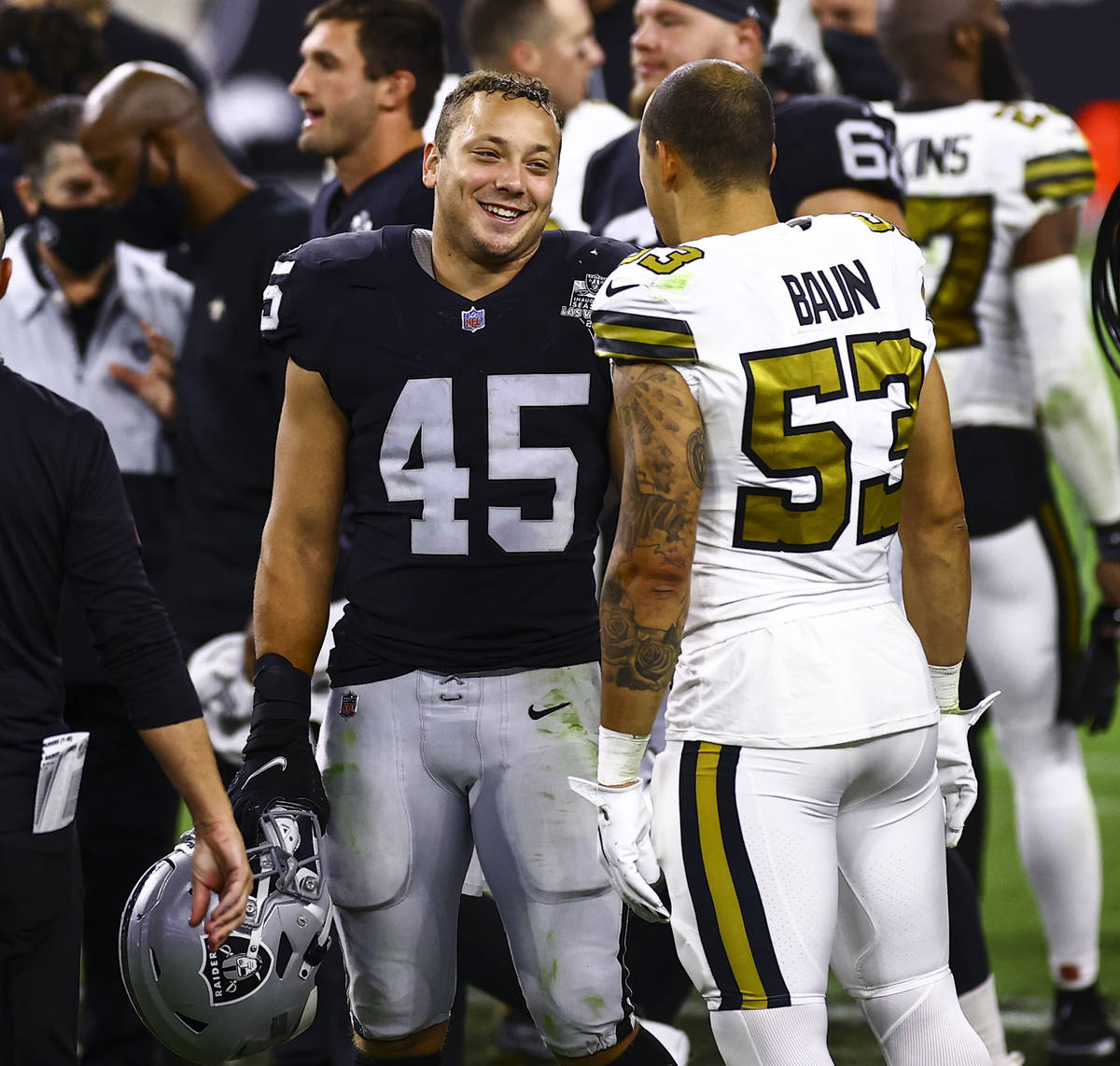 Las Vegas Raiders fullback Alec Ingold (45) talks with New Orleans Saints linebacker Zack Baun ...