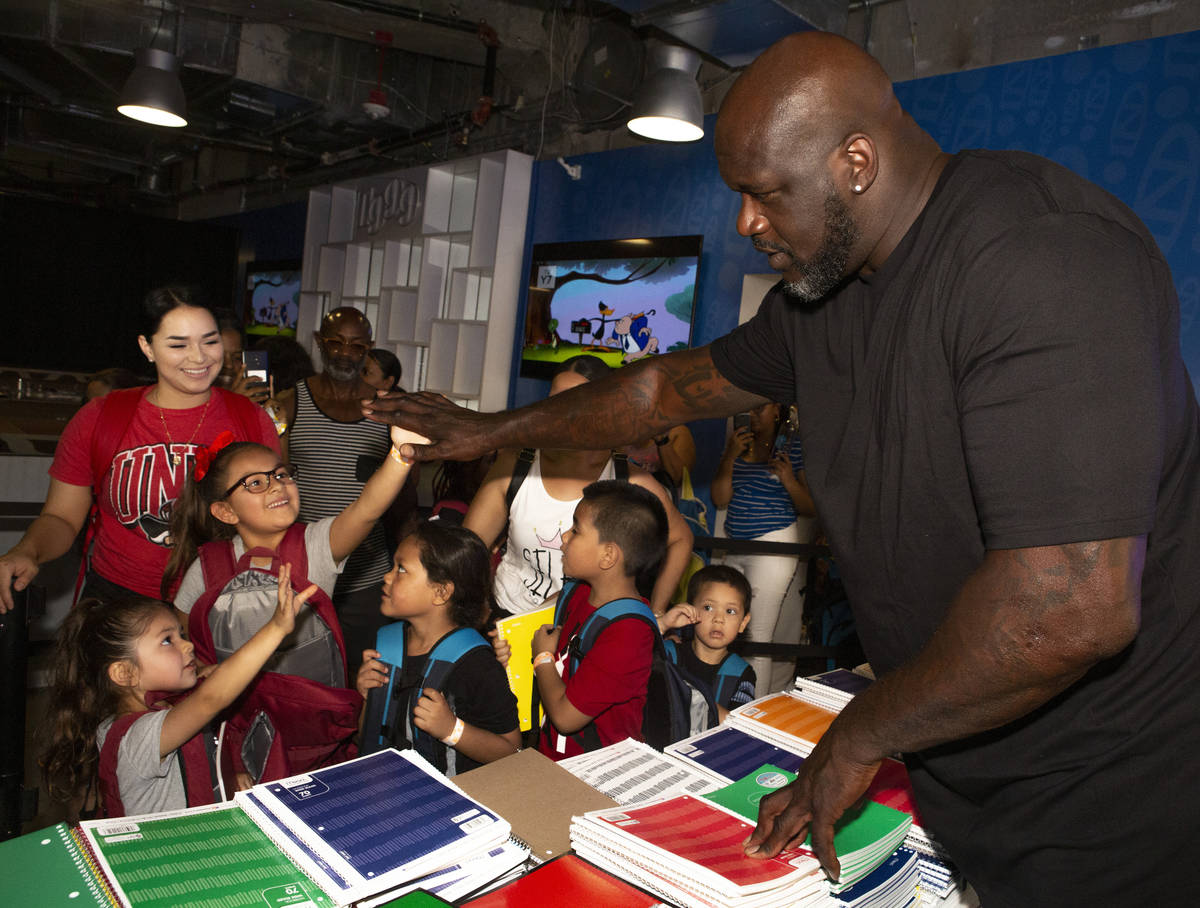 Isabella Hidalgo, 7, center, gives a high-five to former NBA star Shaquille O'Neal, while her s ...