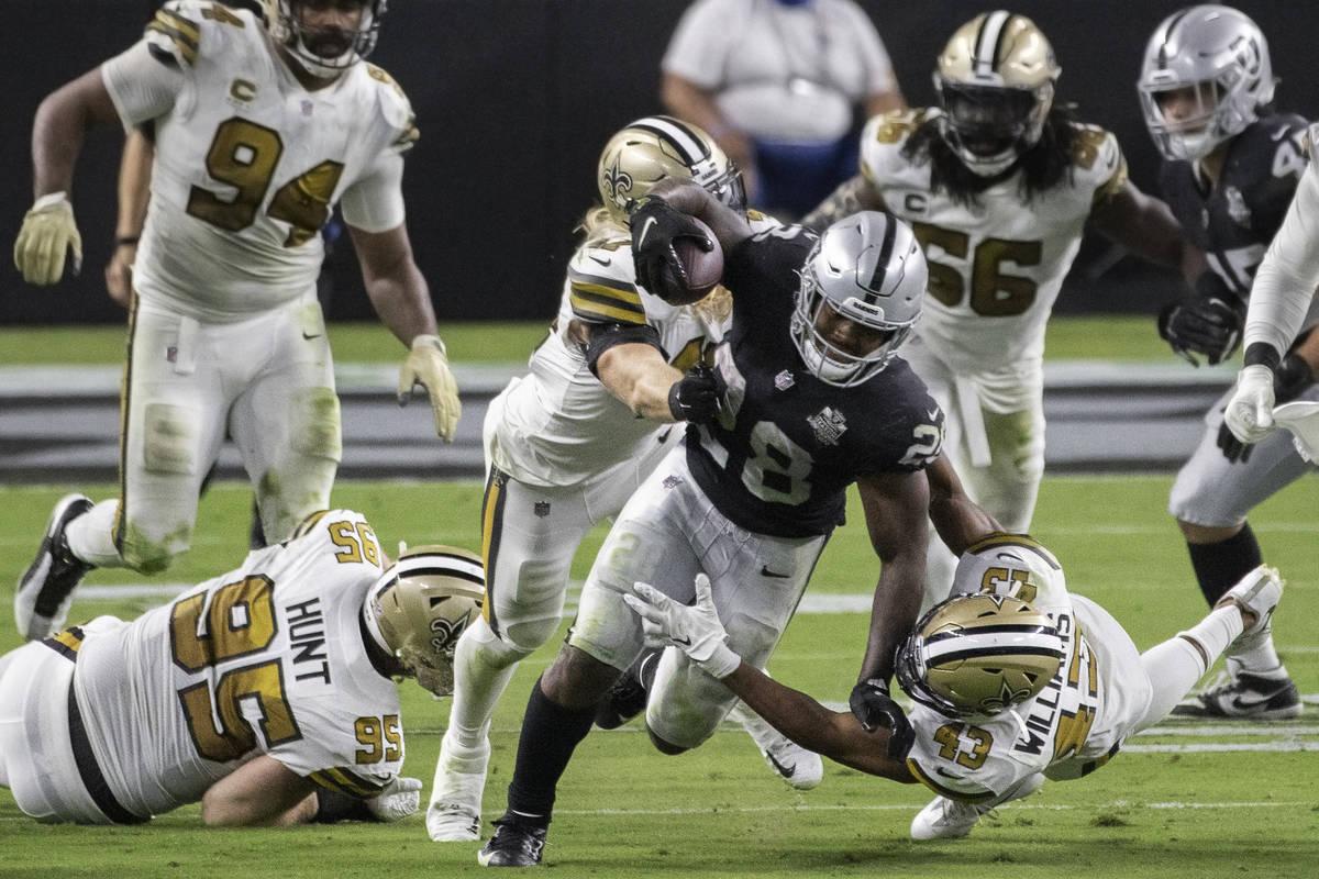 Las Vegas Raiders running back Josh Jacobs (28) breaks free from New Orleans Saints defensive e ...