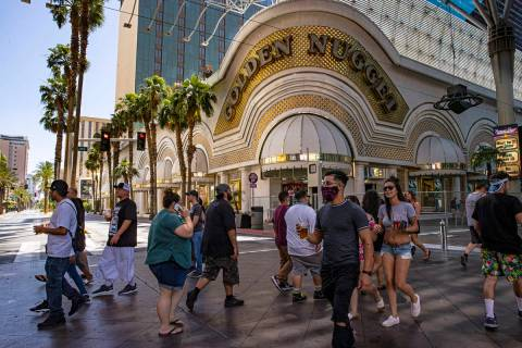 People walk outside of the Golden Nugget at the Fremont Street Experience in downtown Las Vegas ...