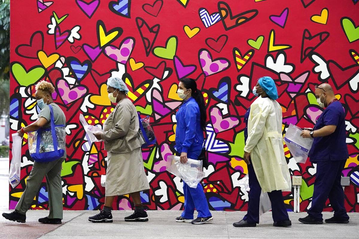 Healthcare workers line up for free personal protective equipment in front of a mural by artist ...