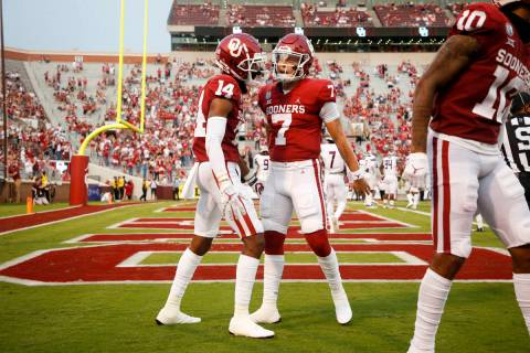 Oklahoma wide receiver Charleston Rambo (14) and quarterback Spencer Rattler (7) celebrate afte ...