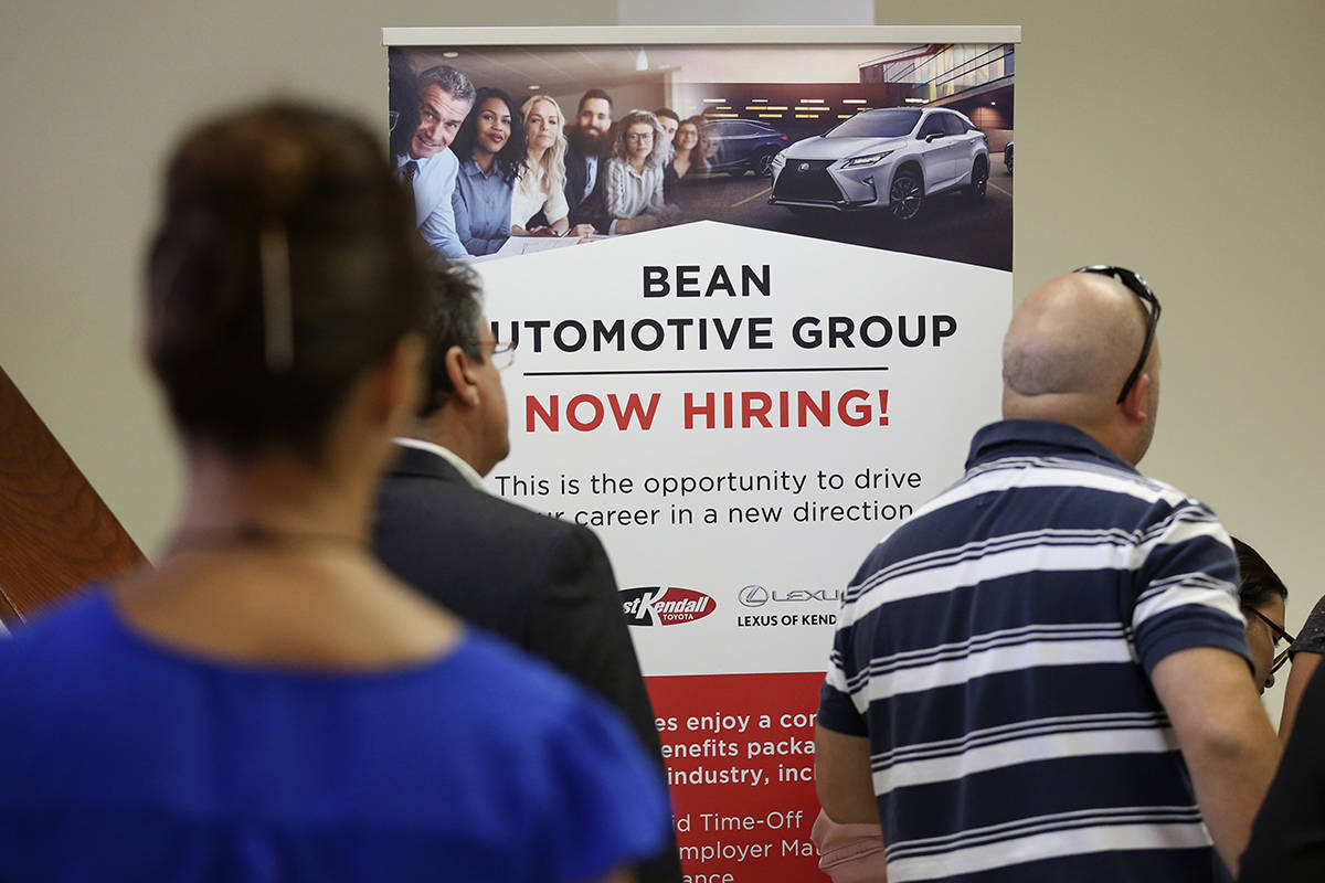 FILE - In this Sept. 18, 2019, file photo people stand in line to inquire about jobs available ...
