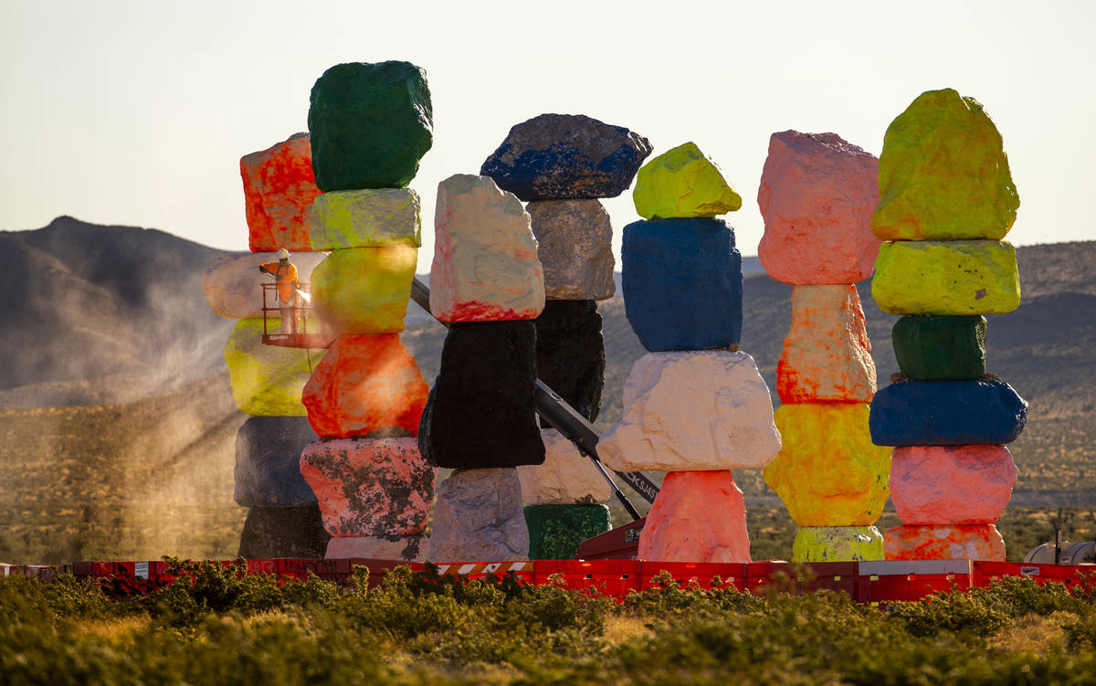 Ivan Ibarra with Vergith Contracting Co. prepares the Seven Magic Mountains for new paint by pr ...