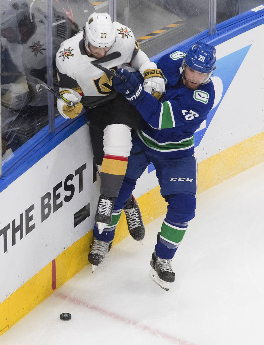 Vegas Golden Knights' Shea Theodore (27) is checked by Vancouver Canucks' Antoine Roussel (26) ...