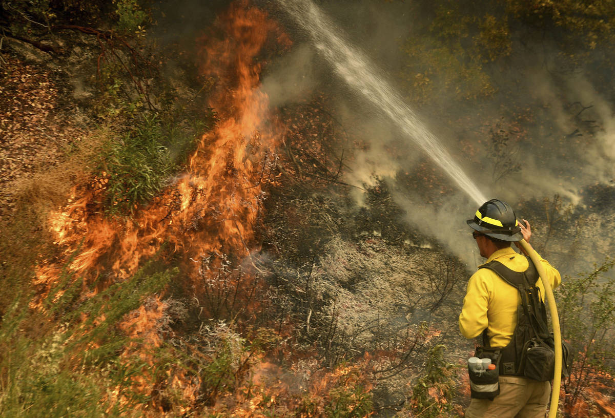 A firefighter puts out a hot spot along Highway 38 northwest of Forrest Falls, Calif., as the E ...
