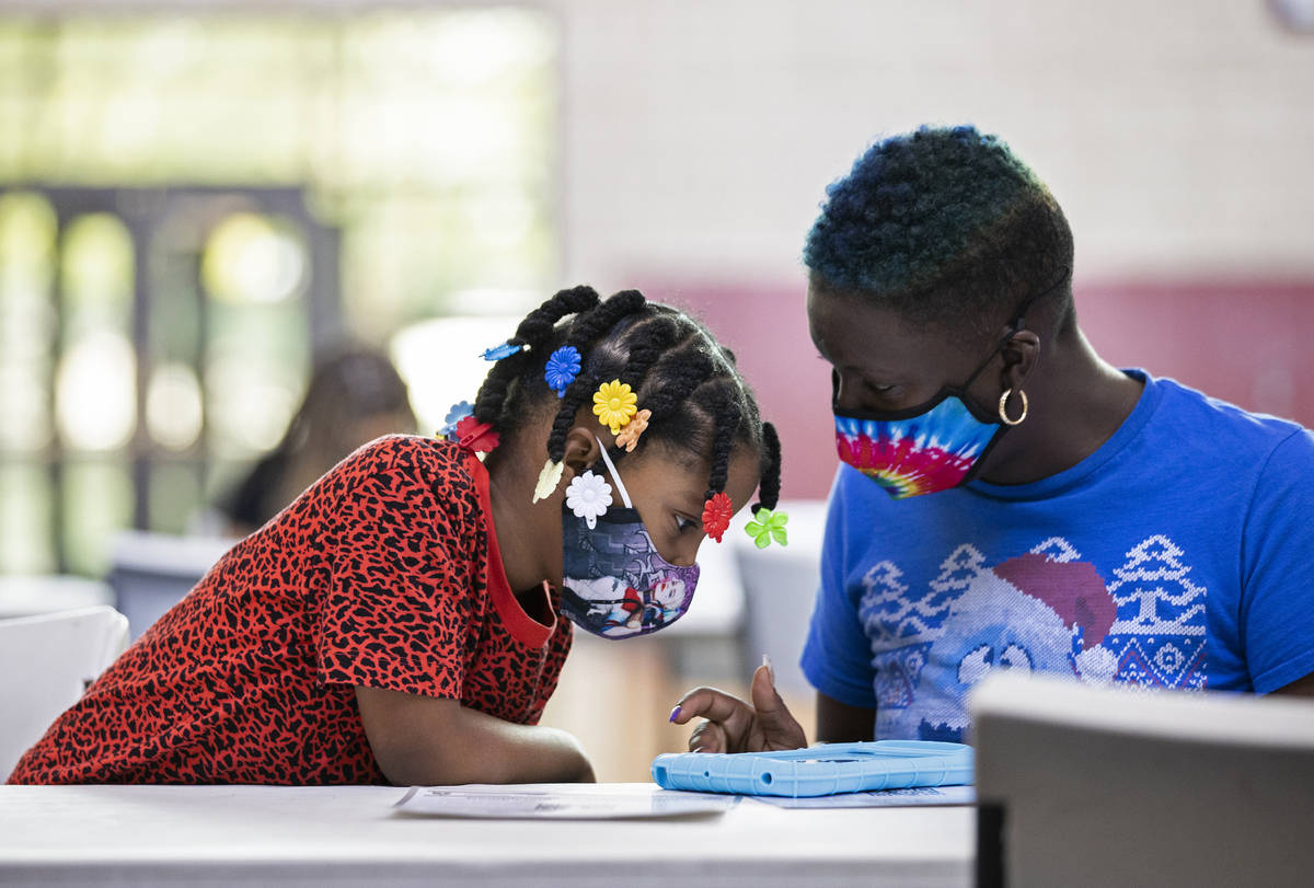 Kanita Carter, right, explains the process of registering to vote to Kimberly Moore, 7, during ...
