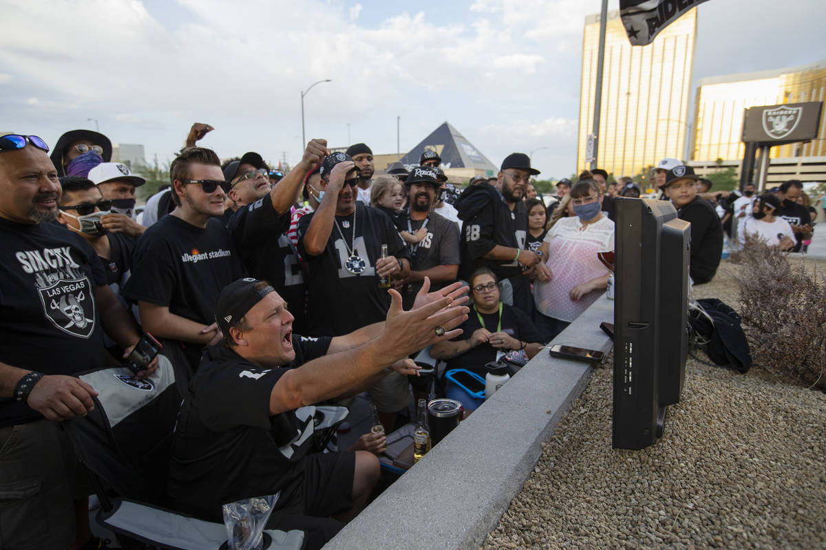 Kenna James, left, and a group that gathered around his TV react to a call during the first hom ...
