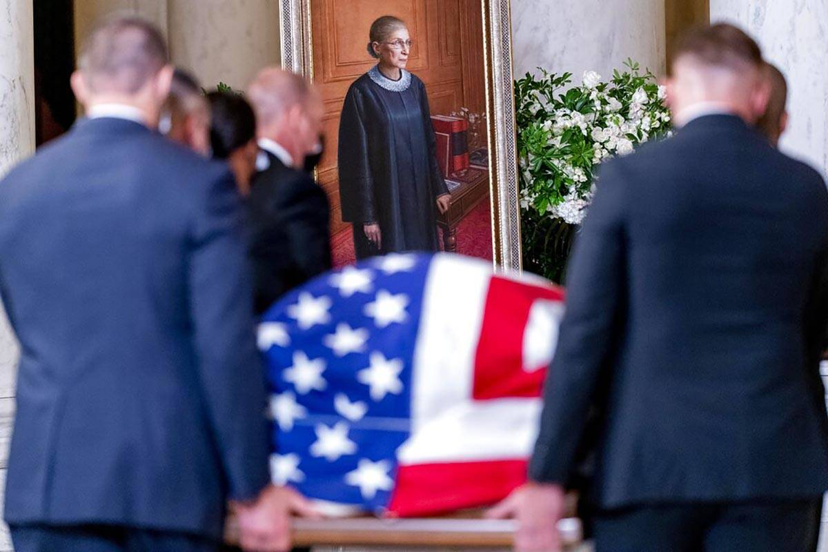 The flag-draped casket of Justice Ruth Bader Ginsburg, carried by Supreme Court police officers ...