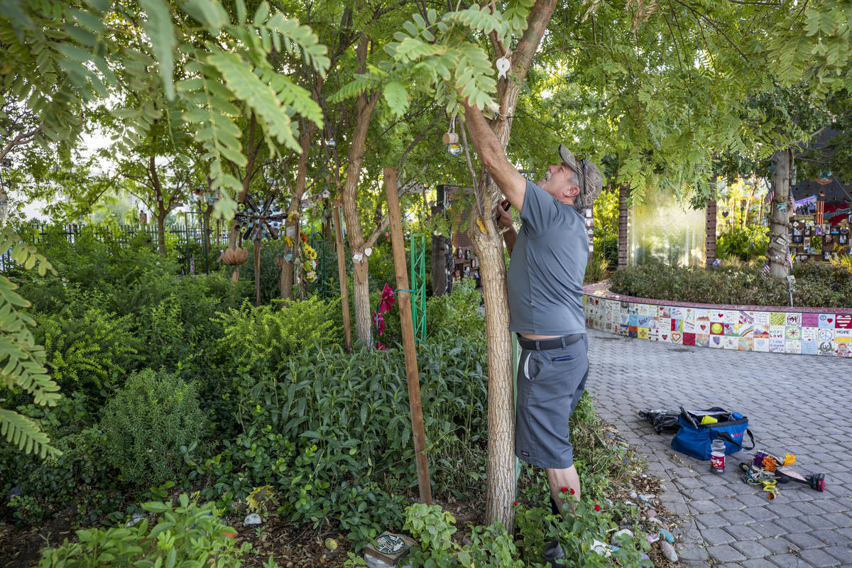 Eddie Schmitz, a volunteer that restores and upkeeps the Las Vegas Healing Garden, carefully ta ...